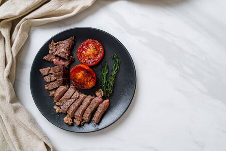 Grilled medium rare beef steak with tomatoes