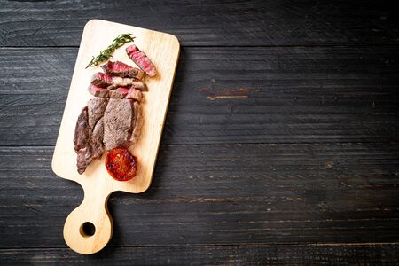 Grilled medium rare beef steak on wood board