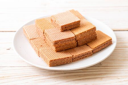 chocolate wafers with chocolate cream on wood background