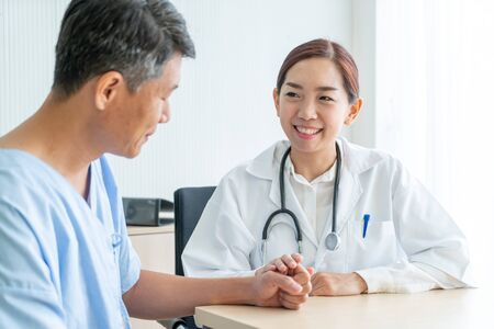 Asian female doctor and patient discussing something while sitting at the table - selective focus point