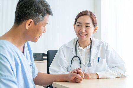 Medico femminile asiatico e paziente discutendo qualcosa mentre sedendosi al tavolo - punto di messa a fuoco selettiva