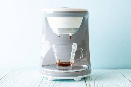 coffee maker machine making coffee on wood background
