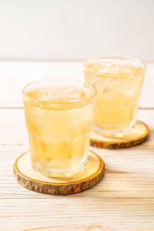 在木背景的被冰的茉莉花茶
