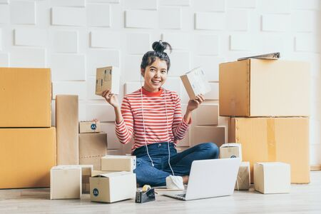 Geschäftsinhaberin asiatischer Frauen, die zu Hause mit Verpackungsbox am Arbeitsplatz arbeitet - Online-Shopping-KMU-Unternehmer oder Online-Verkaufskonzept