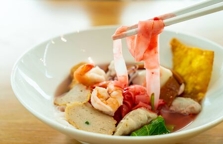 Pink seafood flat noodles (Yen Ta Fo) in white bowl