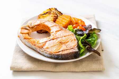 grilled salmon steak fillet with vegetable and french fries on plate