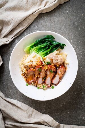 egg noodle with red roasted pork and wonton - Asian food style Stock Photo