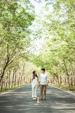 Happy Asian couple in love on road with beautiful tree arch
