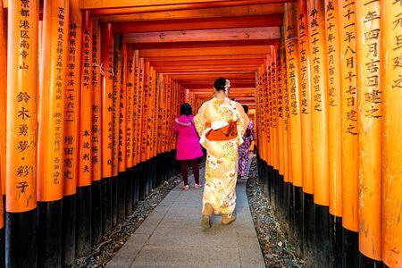 Kyoto, Japan - Jan 11, 2020 : Red Torii gates at Fushimi Inari Taisha with tourists and Japanese students. Fushimi Inari is the most important Shinto sanctuary.