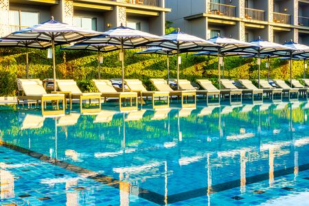 Umbrella and pool bed around outdoor swimming pool in hotel resort for travel holiday vacation concept Editorial