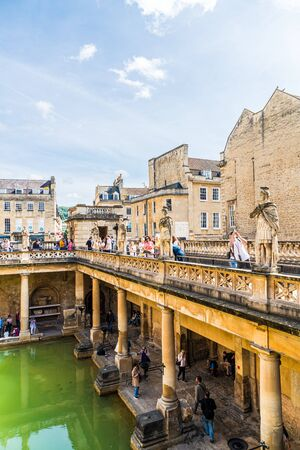 BATH, ENGLAND - AUG 30, 2019 : Roman Baths, the World Heritage site with people, which is a site of historical interest in the city of Bath, United Kingdom.