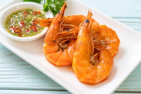 baked salted shrimps or prawns with seafood spicy sauce - seafood style