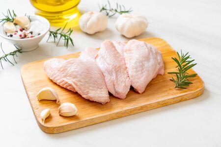Alas de pollo medio crudo fresco sobre tabla de madera con ingredientes