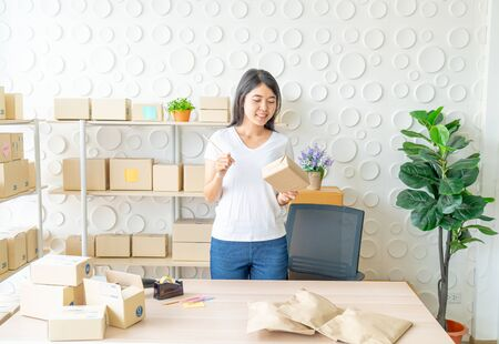 Asian Women business owner working at home with packing box on workplace - online shopping SME entrepreneur or freelance working concept Stock Photo