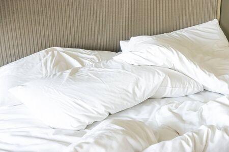 Bałagan na łóżku, biała poduszka z kocem na niepościelonym łóżku