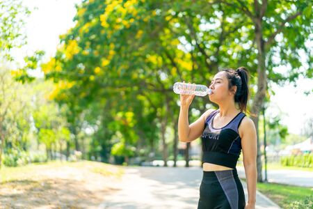 Asian woman drinking water in sportwear after exercise at park Imagens