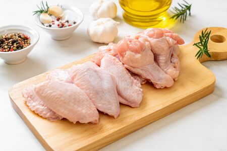 fresh raw chicken wings on wooden board with ingredients
