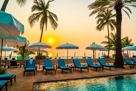 Beautiful palm tree with umbrella chair pool in luxury hotel resort at sunrise times