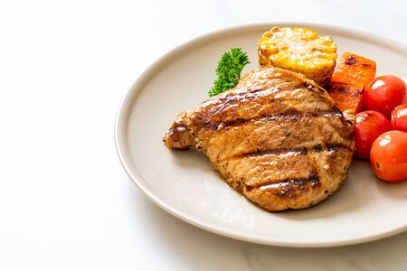 grilled and barbecue fillet pork steak with corn, carrot and tomatoes
