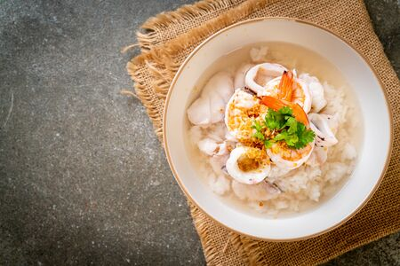 porridge or boiled rice soup with seafood (shrimps, squid and fish) bowl