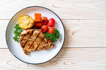 grilled and barbecue fillet pork steak with corn, carrot and tomatoes Foto de archivo