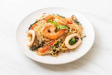 gebratene chinesische Nudeln mit Basilikum, Chili, Shrimps und Tintenfisch - asiatische Küche Standard-Bild