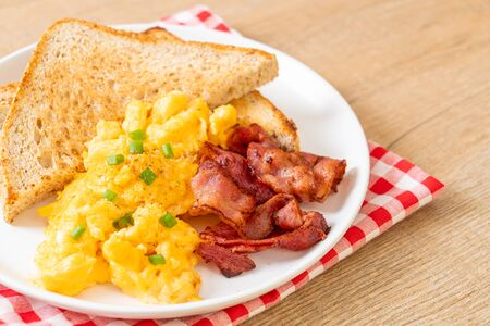 scrambled egg with bread toasted and bacon for breakfast