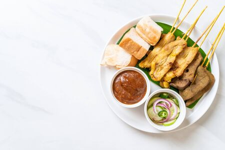Pork Satay and Liver Satay with Bread and Peanut Sauce  and pickles which are cucumber slices and onions in vinegar - Asian food style Standard-Bild