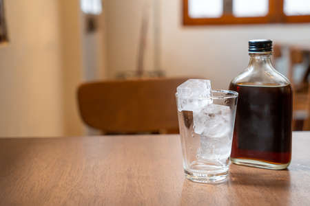 ice cube in glass with cold brew coffee on wood table