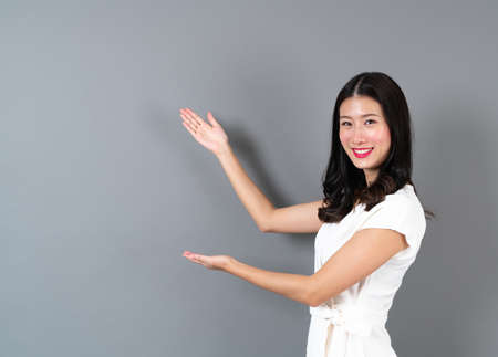 Young asian woman with smiling face and hand presenting on side in grey background