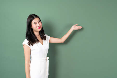 Young asian woman with smiling face and hand presenting on side in green background 版權商用圖片