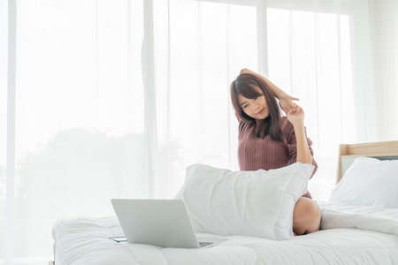 Asian women working with laptop on bed at home Banque d'images