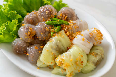 The transparent balls are called Saku Sai Moo or Steamed Tapioca Dumplings Ball with Pork Filling and ( Kow Griep Pag Mor)Pork Steamed Rice Parcels or Steamed Rice-Skin Dumplings