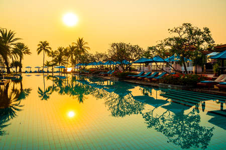 beautiful palm tree with umbrella chair pool in luxury hotel resort at sunrise times - holiday and vacation concept Archivio Fotografico