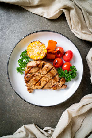 grilled and barbecue fillet pork steak with corn, carrot and tomatoes Banque d'images