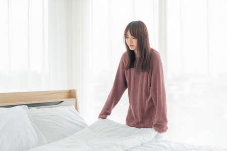 beautiful Asian women making bed in room with white clean sheet 写真素材