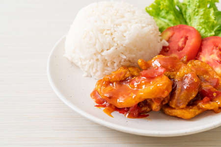 Fried fish topped by 3 flavors chili sauce with rice on white plate Standard-Bild