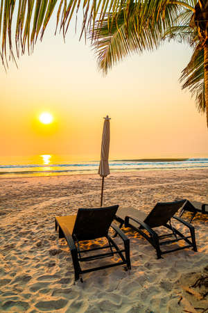 umbrella chair beach with palm tree and sea beach at sunrise times - vacation and holiday concept Foto de archivo