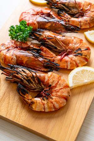 grilled tiger prawns or shrimps with lemon on wood board