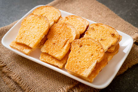 baked crispy bread with butter and sugar on plate