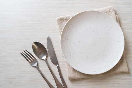 empty plate or dish with knife, fork and spoon on wood tile background Stockfoto