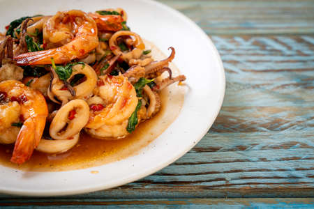 stir-fried seafood (shrimps and squid) with Thai basil - Asian food style Archivio Fotografico