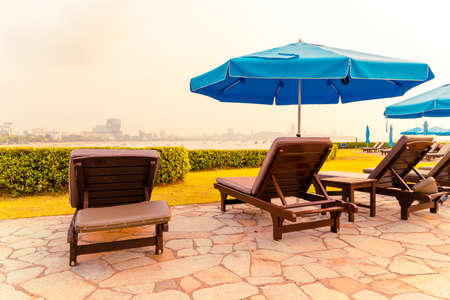 beach chair or pool bed with umbrella around swimming pool with sunset and sea background
