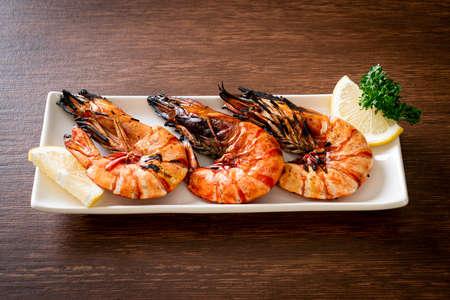 grilled tiger prawns or shrimps with lemon on plate