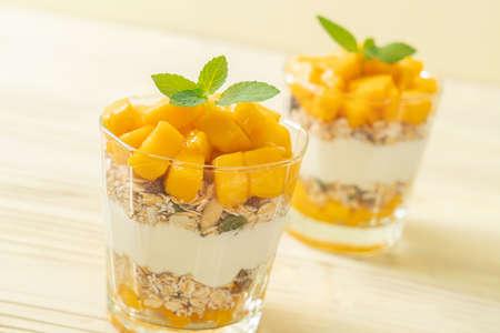fresh mango yogurt with granola in glass - healthy food style Foto de archivo