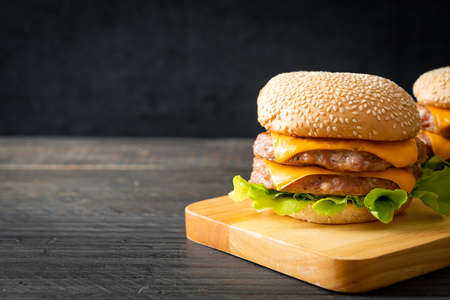 pork hamburger or pork burger with cheese on wooden board Foto de archivo
