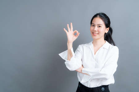 Young Asian woman smiling and showing OK sign on grey background Stockfoto