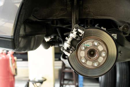 Disc car close up - mechanic unscrewing automobile parts while working under a lifted auto - Car service concept Foto de archivo