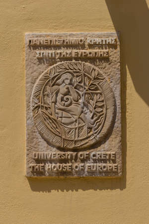 Rethymno, Greece - July 30, 2016: University of Crete plate on the house. The University of Crete is the principal higher education institution on the island of Crete, Greece, and one of the country's most academically acclaimed and reputable ones.
