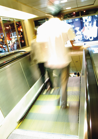 unknown age: Rear view of a man on an escalator moving walkway Stock Photo